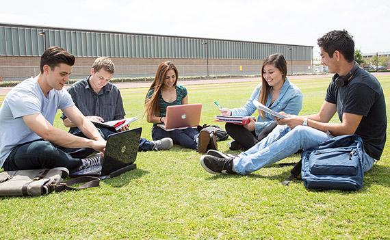 students with computers on field