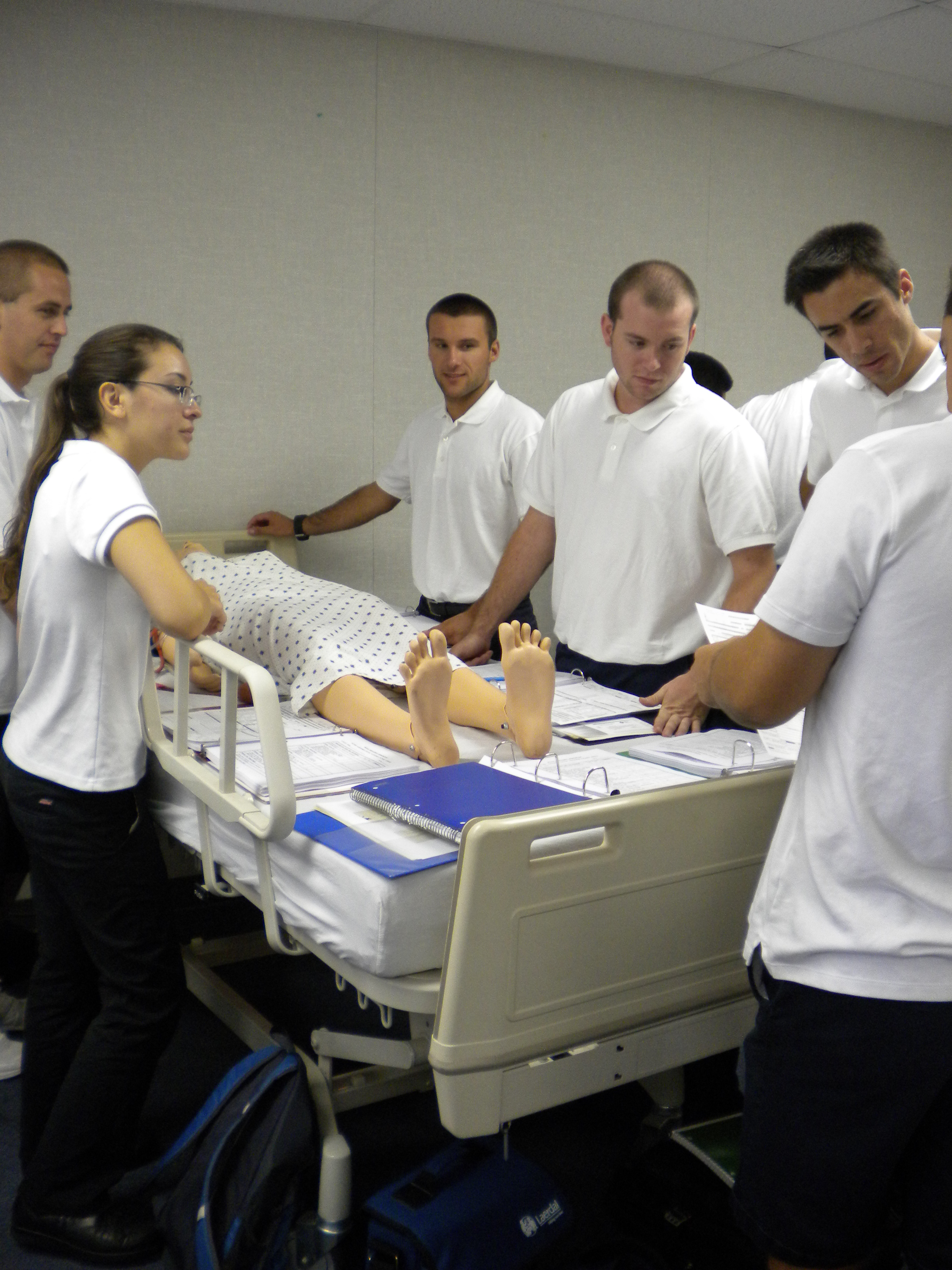 Several students wearing EMT uniform (white polo, black pants), observing a mannequin