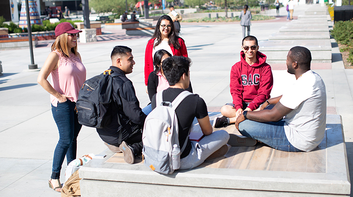 Seven SAC students hang out around the campus plaza.